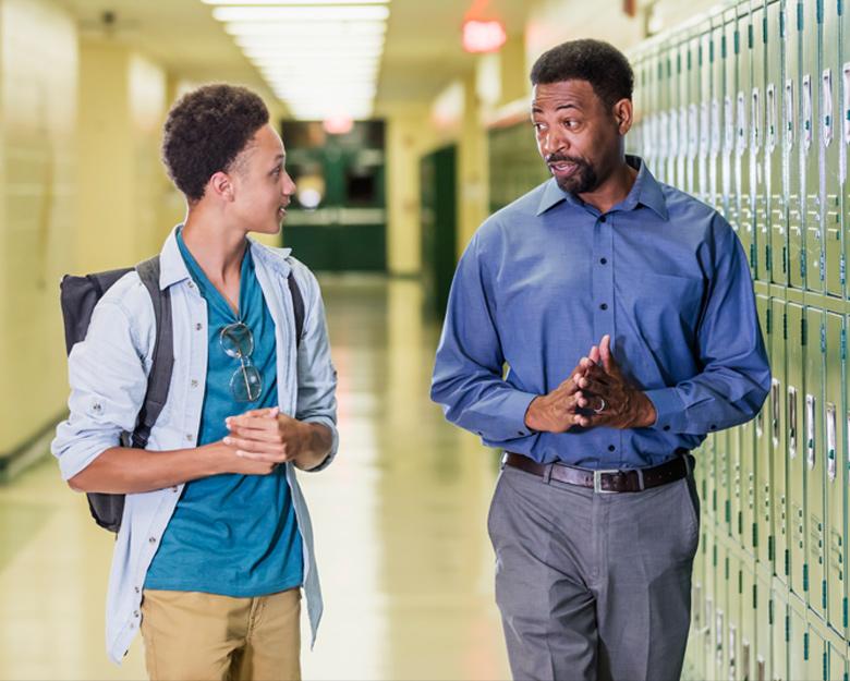a student walks with his principal down a school hallway